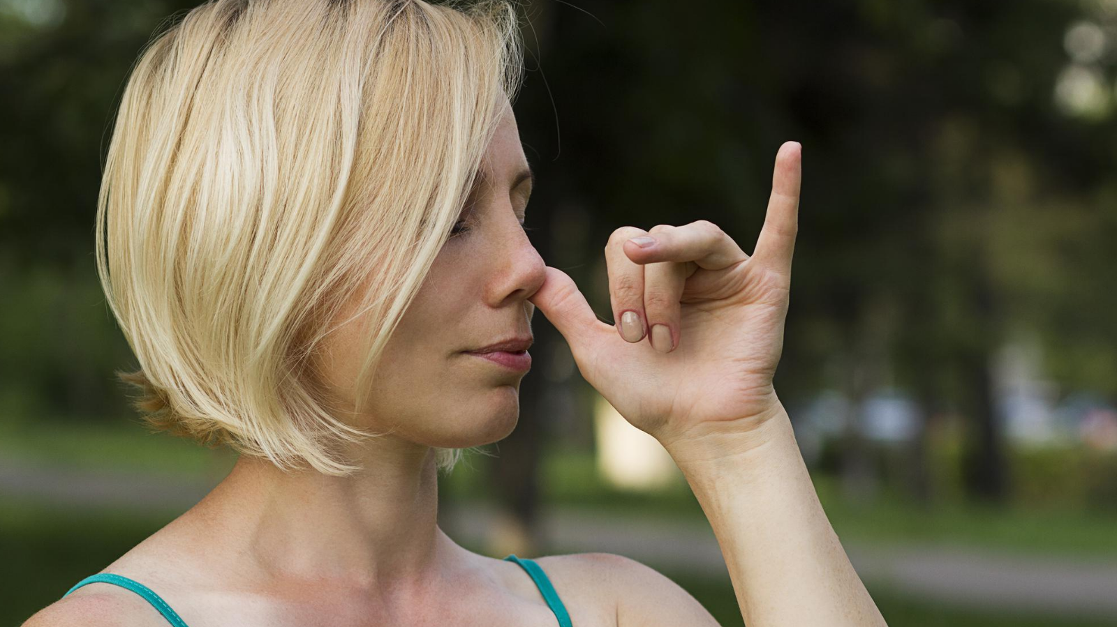 A woman practicing pranayama breathing during yoga practice to experience the benefits of reduced stress and anxiety