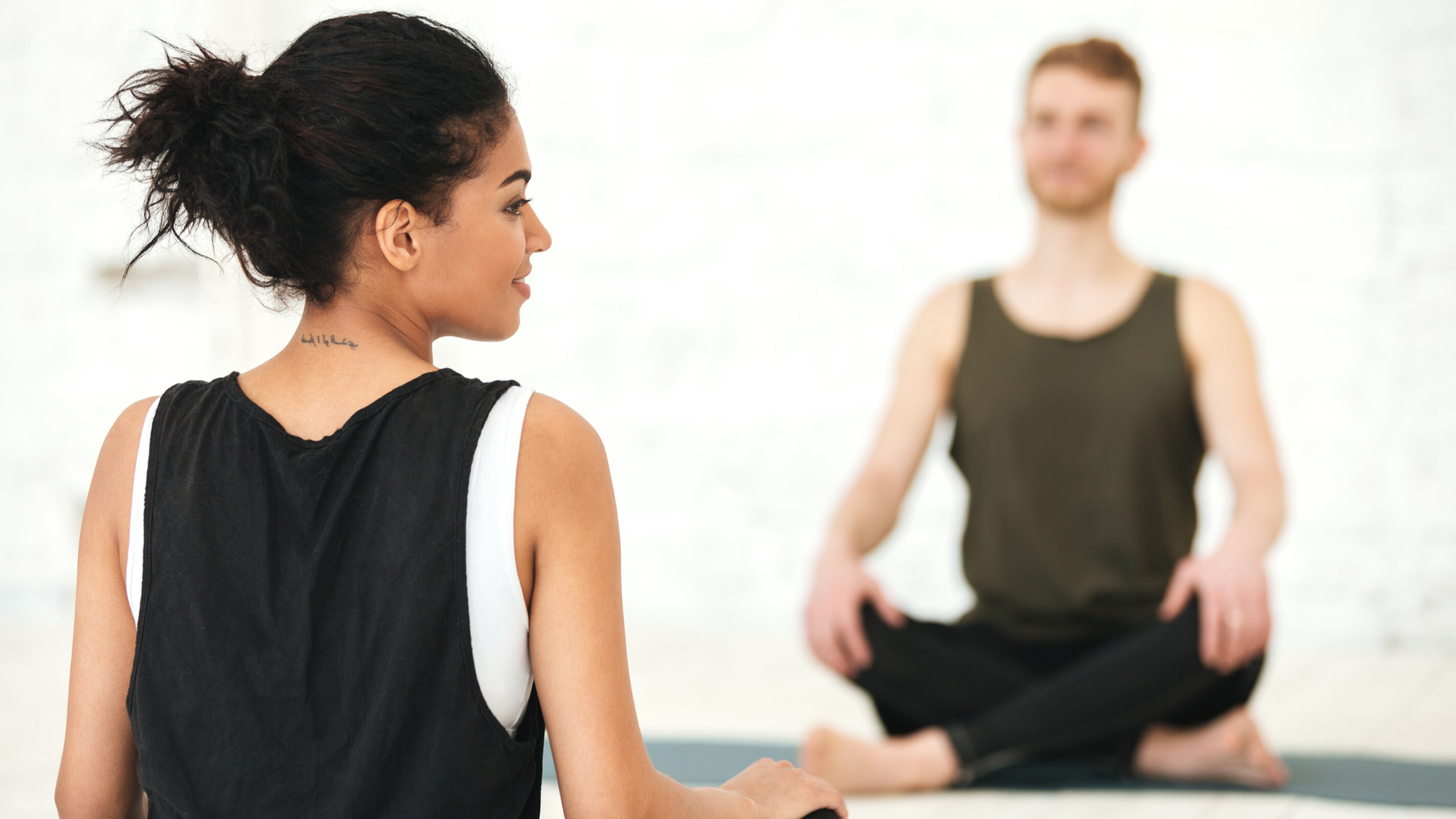 Female yoga teacher guiding her yoga student in mindful practice.
